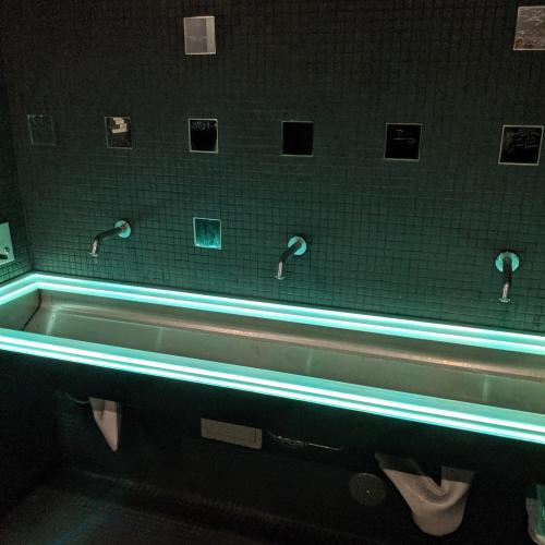 A wide trough sink lined with LEDs at Ground Kontrol. Small square mirrors line the wall above.